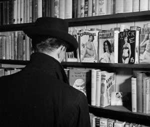 A man looks at the pornography section at a Soho sex shop in London, 1956